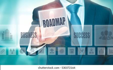A businessman pressing a Roadmap button on a transparent screen.