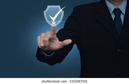 Businessman pressing security shield with check mark icon over gradient light blue background, Technology computer and internet cyber security  and anti virus concept