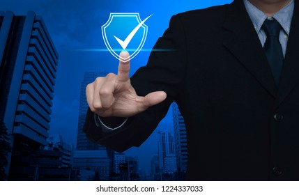 Businessman pressing security shield with check mark icon over modern office city tower and skyscraper, Technology computer cyber security and anti virus concept