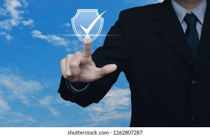 Businessman pressing security shield with check mark icon over blue sky with white clouds, Technology computer cyber security and anti virus concept
