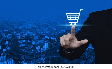 Businessman pressing shopping cart icon over city tower and street blue tone background, Shop online concept