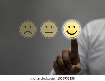 Businessman pressing smiley face touch screen / Business Service Satisfaction concept