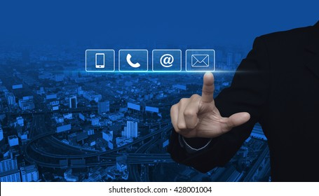 Businessman pressing telephone, mobile phone, at and email buttons over city tower and street blue tone background, Customer support concept