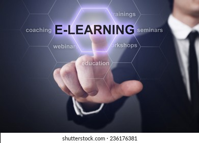 Businessman pressing touch screen interface and select E-learning. E-learning education concept