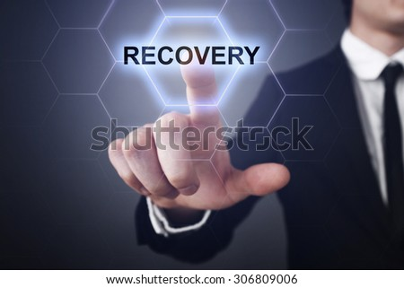 "Businessman pressing touch screen interface and select icon ""recovery"". Business concept. Internet concept."