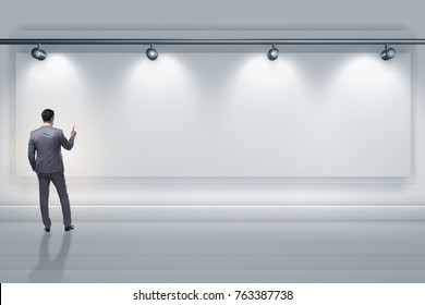 Businessman pressing virtual button on the wall lit with spotlig