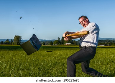 A businessman or IT professional takes a swing at a laptop with a baseball bat.