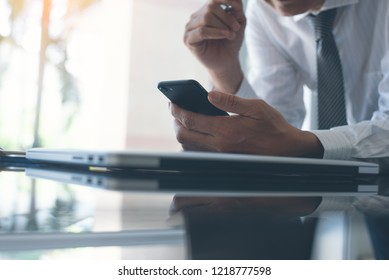 Businessman, project manager browsing internet on smart mobile phone, working on laptop computer with notebook on office desk in modern office, close up, business and financial concept