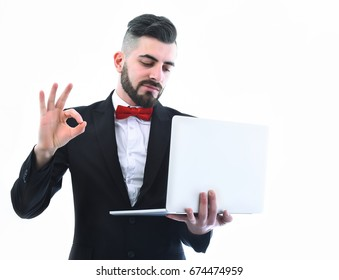 Businessman or project manager with smile on his face and beard shows OK sign and looks at white laptop, isolated on white background, copy space. Concept of success and high tech era