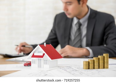 Businessman as a property agent or investor calculating growth of return on investment in real estate with house model, blueprints and money on the table at his office