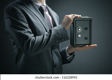 Businessman protecting his savings in the safe