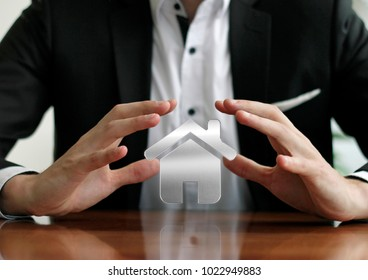 Businessman protecting house with hands
