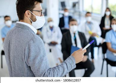 Businessman with protective face mask holding a seminar to large group of people in convention center.