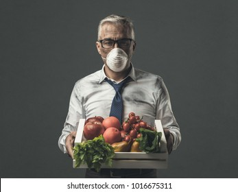 Businessman with protective mask holding a crate with polluted poisonus vegetables, food pollution concept