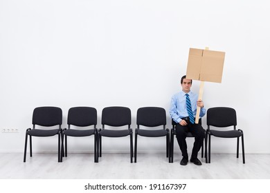 Businessman protesting alone - sitting on chairs row with blank sign