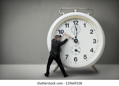 Businessman pulling a clock hand backwards
