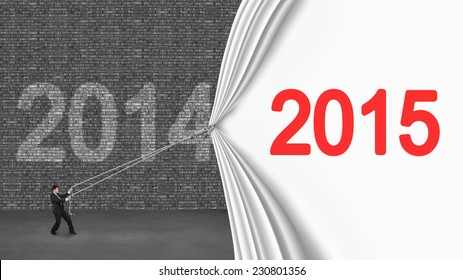 businessman pulling down 2015 curtain covering old 2014 brick wall on gray concrete floor