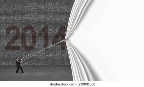 businessman pulling down white blank curtain covering old 2014 brick wall on gray concrete floor