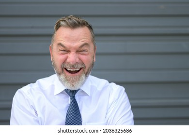 Businessman pulling a funny face screwing up his eyes with an expression of anguish while standing in front of a grey exterior wall