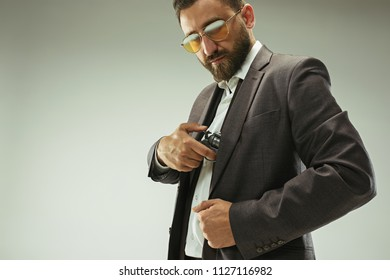 Businessman pulling the gun out of pocket. Stylish rich business man on gray studio background. Italian look