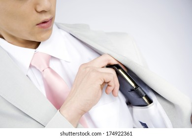 businessman pulling a notebook from the breast pocket