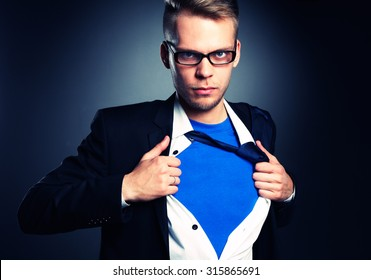 Businessman pulling open his shirt like a superhero