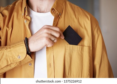 Businessman pulling out business card from pocket of his denim jacket, exchanging information with a potential partner. Mockup Copy Paste Blank Advertisement