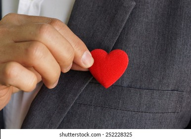 Businessman pulling out a red heart from the pocket of his suit - customer relationship management - service mind