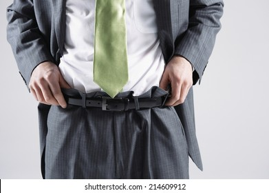 Businessman pulling up pants and fixing his shirt on white background