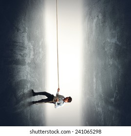 A businessman pulling a rope to climb