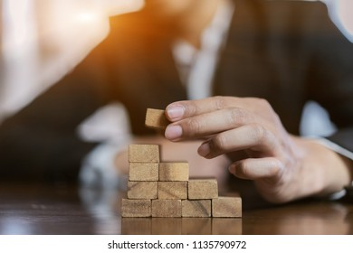 Businessman of pulling wooden block before fail on building tower at home and change, choice business risking dangerous project plan failure construction