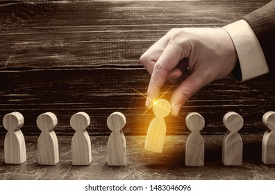 A businessman pulls a glowing golden man figure out of a gray crowd. The concept of search workers for hiring, promotion. Business management. Talented and capable employee, selection of candidates.