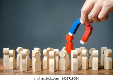 businessman pulls out a red figure of a man from the crowd with the help of a magnet. Increase team efficiency, productivity. leader manages the business and forms a team. toxic, incompetent worker.