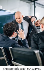 Businessman punching hitting colleague in the face during meeting