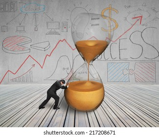 businessman push inclined hourglass on wooden floor with doodles wall