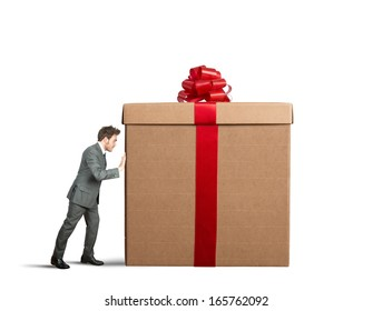 Businessman pushes a big gift on white background