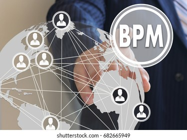 Businessman pushes a button BPM, Business Process Management on the touch screen with a futuristic background.