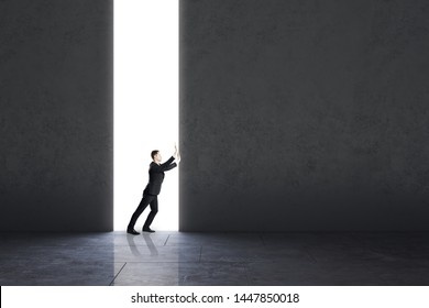 Businessman pushing concrete wall in interior. Opportunity and work concept.