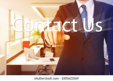 Businessman pushing Contact Us button on virtual screen with burst effect