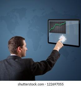 Businessman pushing digital button on tablet screen