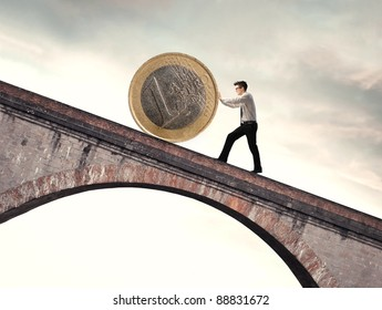 Businessman pushing an euro coin uphill