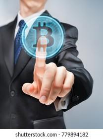 Businessman pushing futuristic bitcoin button