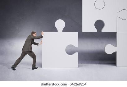 Businessman pushing puzzle piece on grey background