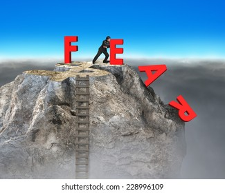businessman pushing red fear word down with dollar sign and wooden ladder on top of rocky mountain, overcoming fear concept.