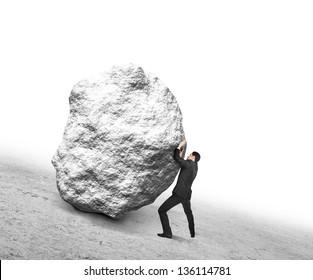 businessman pushing stone up hill