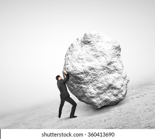 businessman pushing stone up on hill