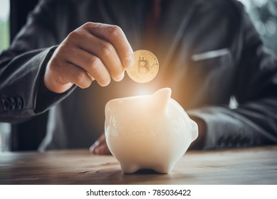 Businessman put bitcoin to piggy bank, bit coin BTC the new virtual electronic money, investment concept