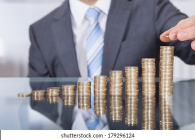 Businessman Put Coin To Highest Stack Of Coins