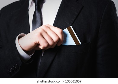 businessman put or take out credit card in pocket, close up on a gray background