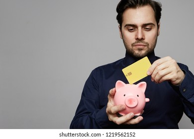 Businessman puts a crredit card in a pink piggy bank